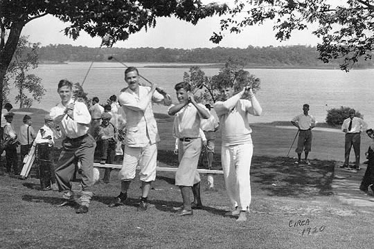 Four golfers posing with their clubs.